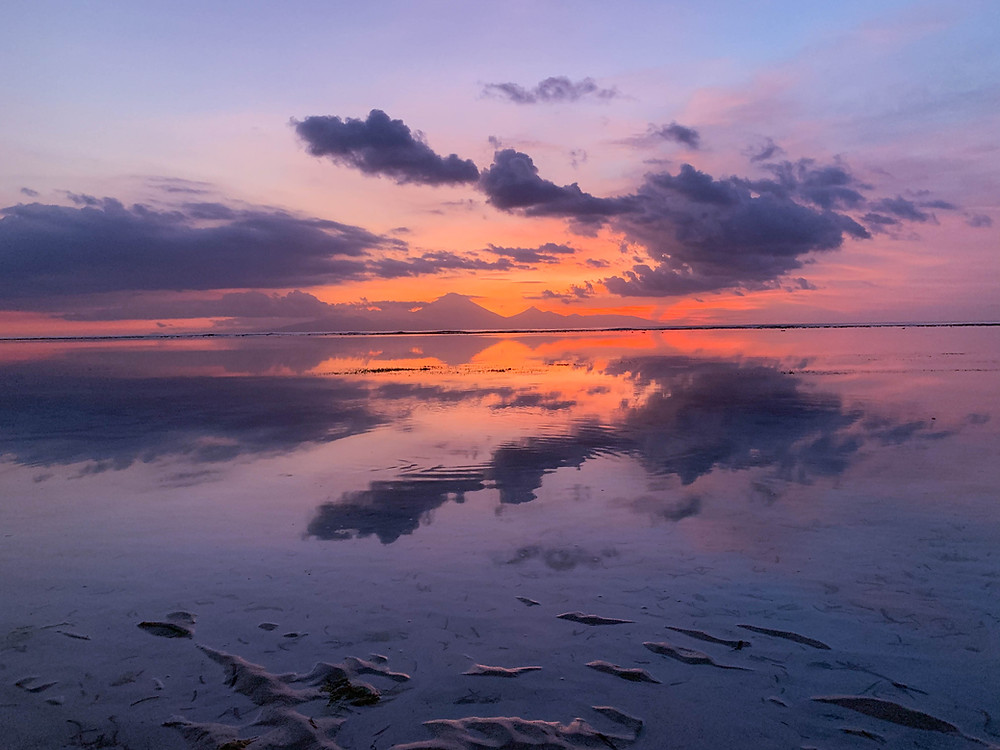 A perfect reflection of Mount Agung in Bali over a purple and pink Gili T sunset