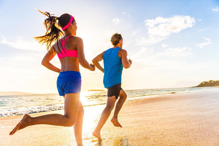 Two athletes running on a white sandy beach in Gili Trawangan