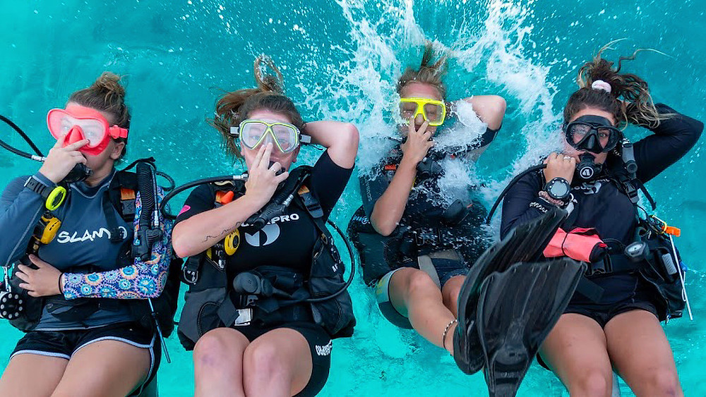Four girls that scuba backrolling into Gili Trawangan turquoise blue waters