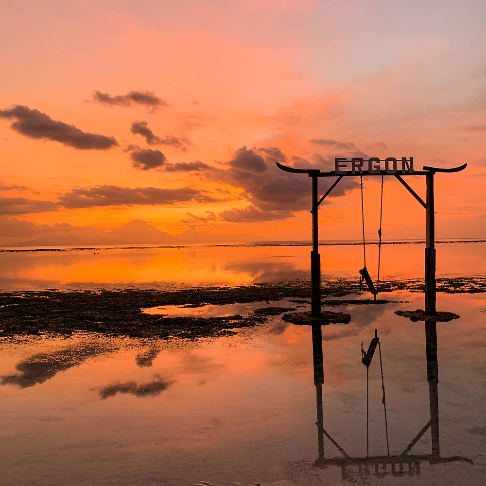 Bright orange sunset and view of Bali as seen from the beaches of Gili T