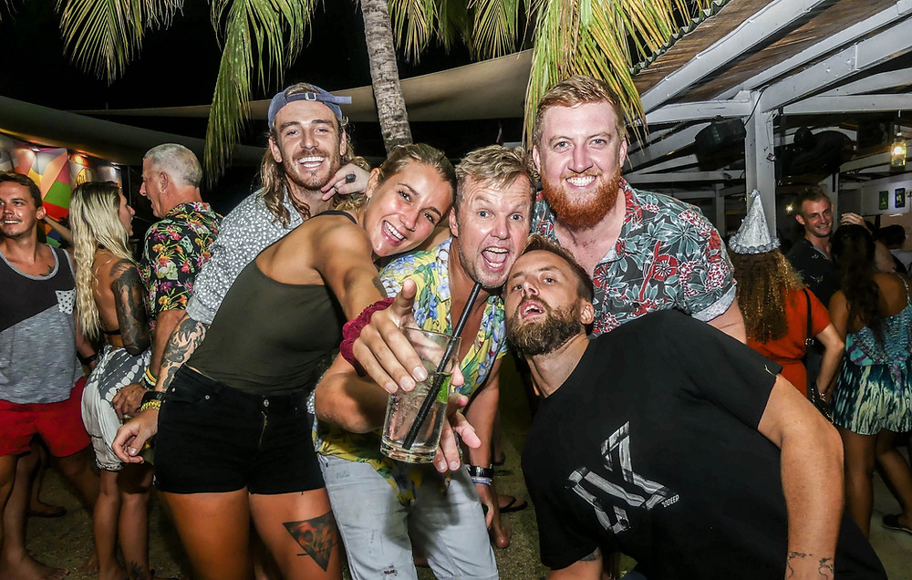 Five festive friends pointing at the camera on a night out in Gili T