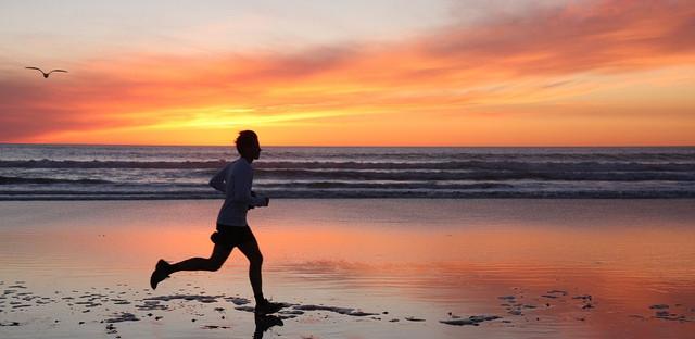 Man running on a beach at sunset