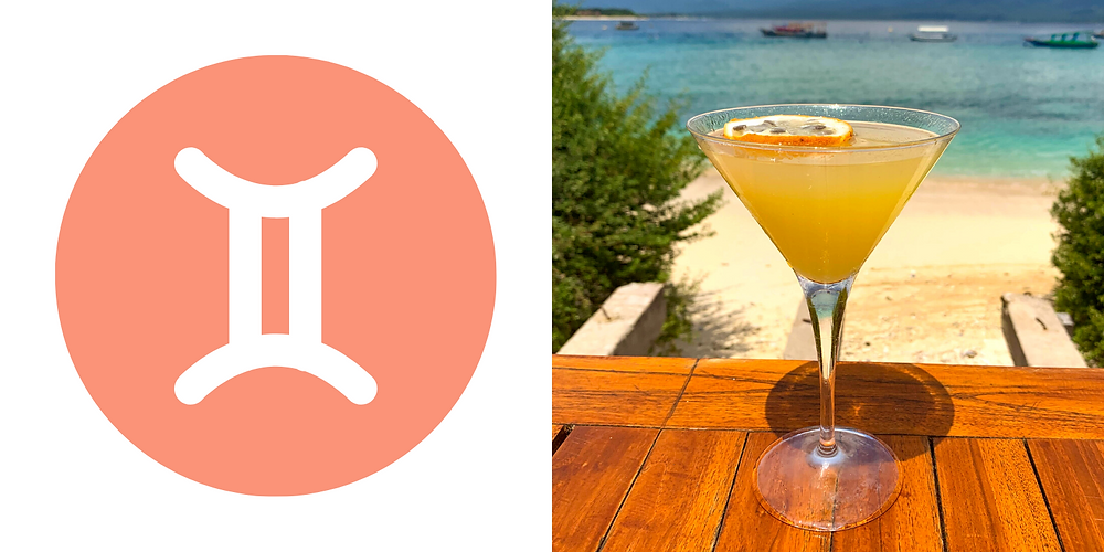 A funny looking orange drinks in a martini glass looking out in the ocean