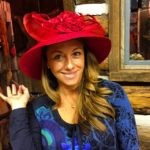 Linda Ruggeri in a blue shirts and a big read fancy hat