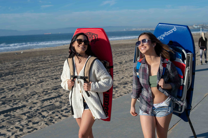 Girls walking on Strand with Beach Porter