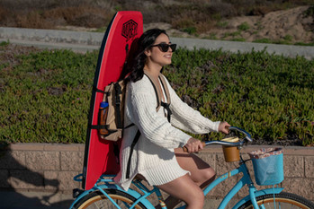 Girl riding bike with Beach Porter and Boogie Board