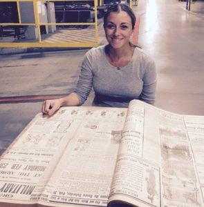 Linda Ruggeri leafing through historic newspapers