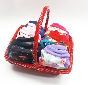 A basket with potty training pants cloth pull ups made of PUL prints of monsters, ice creams, spaceships, rocketships, birds, flowers, robots, construction trucks, cars, fairies, mermaids, cats. ponies, of red, purple, black, blue, green, pink colors
