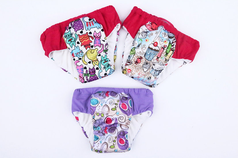 washable overnight diapers of colorful cats, pink and red sweets and purple swirls front view