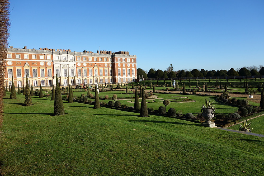 Hampton Court Palace in the background and large green garden in the foreground