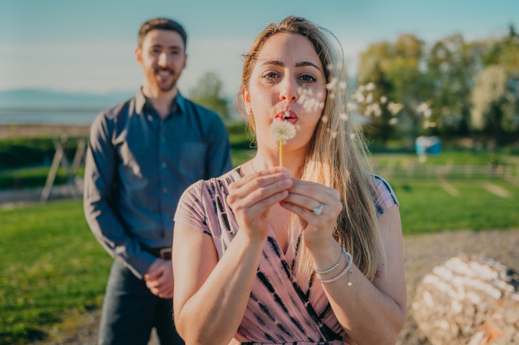 Vancouver-engaged-couple-blowing flower-