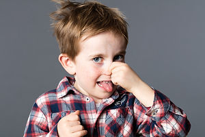 unhappy young boy pinching his nose for