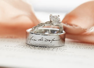 "A custom made, engraved, men's wedding band reading, ""From this day forward"" and a women's dimamond engagement ring"