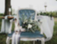 A bride's wedding bouquet on an antique chair in front of a dinner table outside