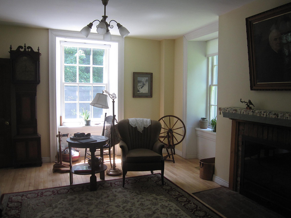 The sitting room in Thistle Ha' farmhouse.  There is a portrait of Jim's great grandfather to the right, and a clock from Scotland to the left.