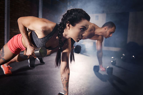 Confident couple working out with dumbbe