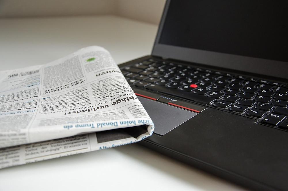 Ordenador portátil y periódico/diario