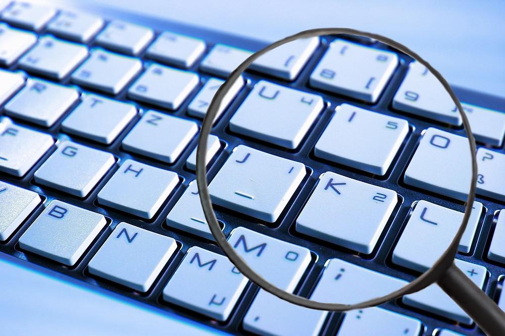 Teclado de ordenador y lupa, seguridad en Internet, privacidad en la Red