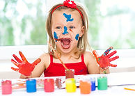 little girl painting with paintbrush and
