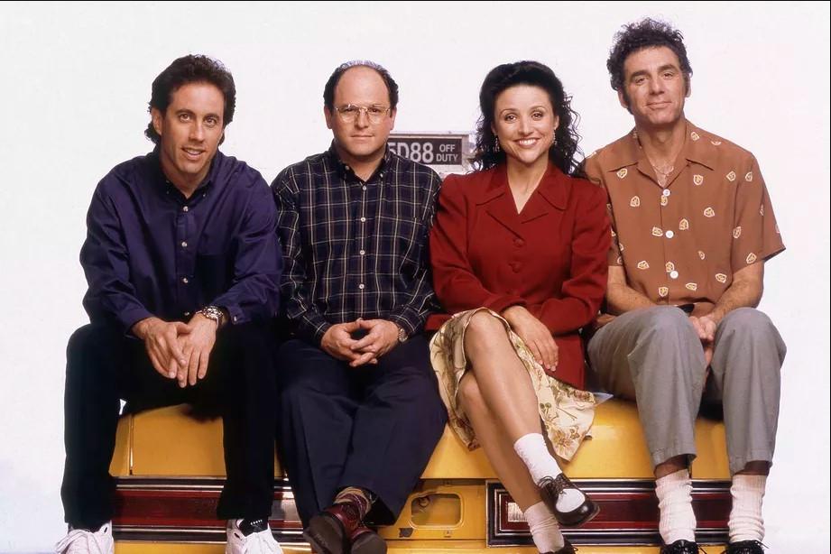 os quatro membros do elenco da série seinfeld sentados no porta malas de um taxi amarelo. Todos vestem roupas largas e de cores sóbrias