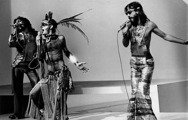 os três membros da banda secos e molhados, com calças justas, penas, paetês e barrigas de fora
