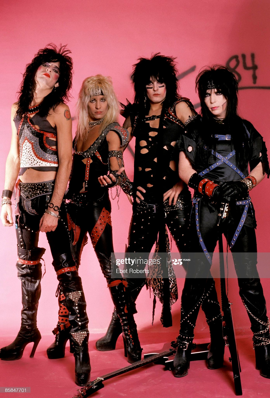 os quatro integrantes do Motley Crue de pé, vestidos em saltos, calças de couro e maquiagem