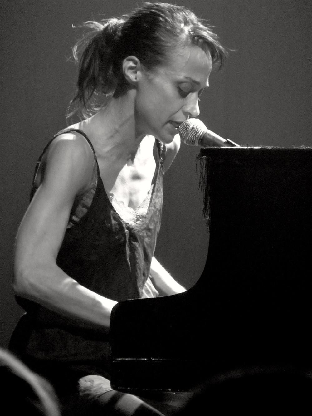 A cantora Fiona Apple sentada tocando piano em uma apresentação ao vivo