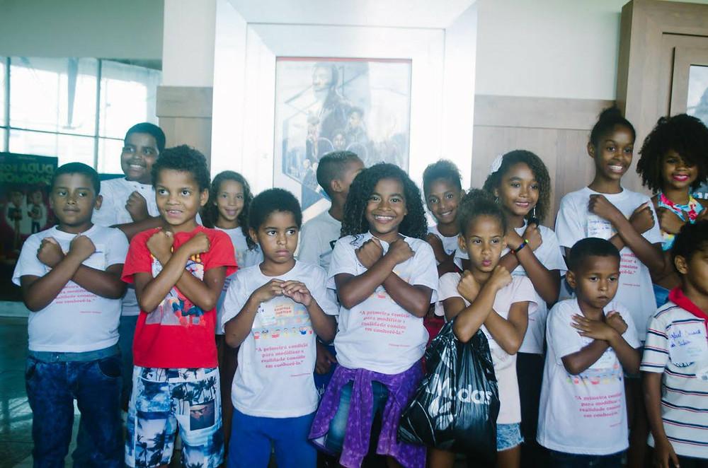 Crianças fazendo o gesto de Wakanda