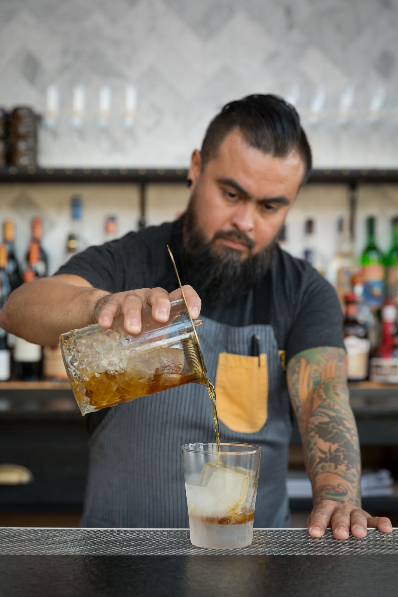 Bartender pouring cocktail at bar