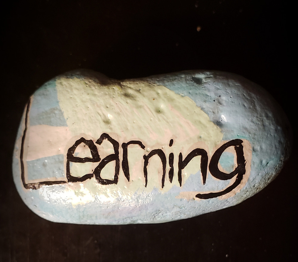 A black background with a painted rock. The background of the rock is painted a light blue and has a tree facing horizontally behind the word Learning in black paint.