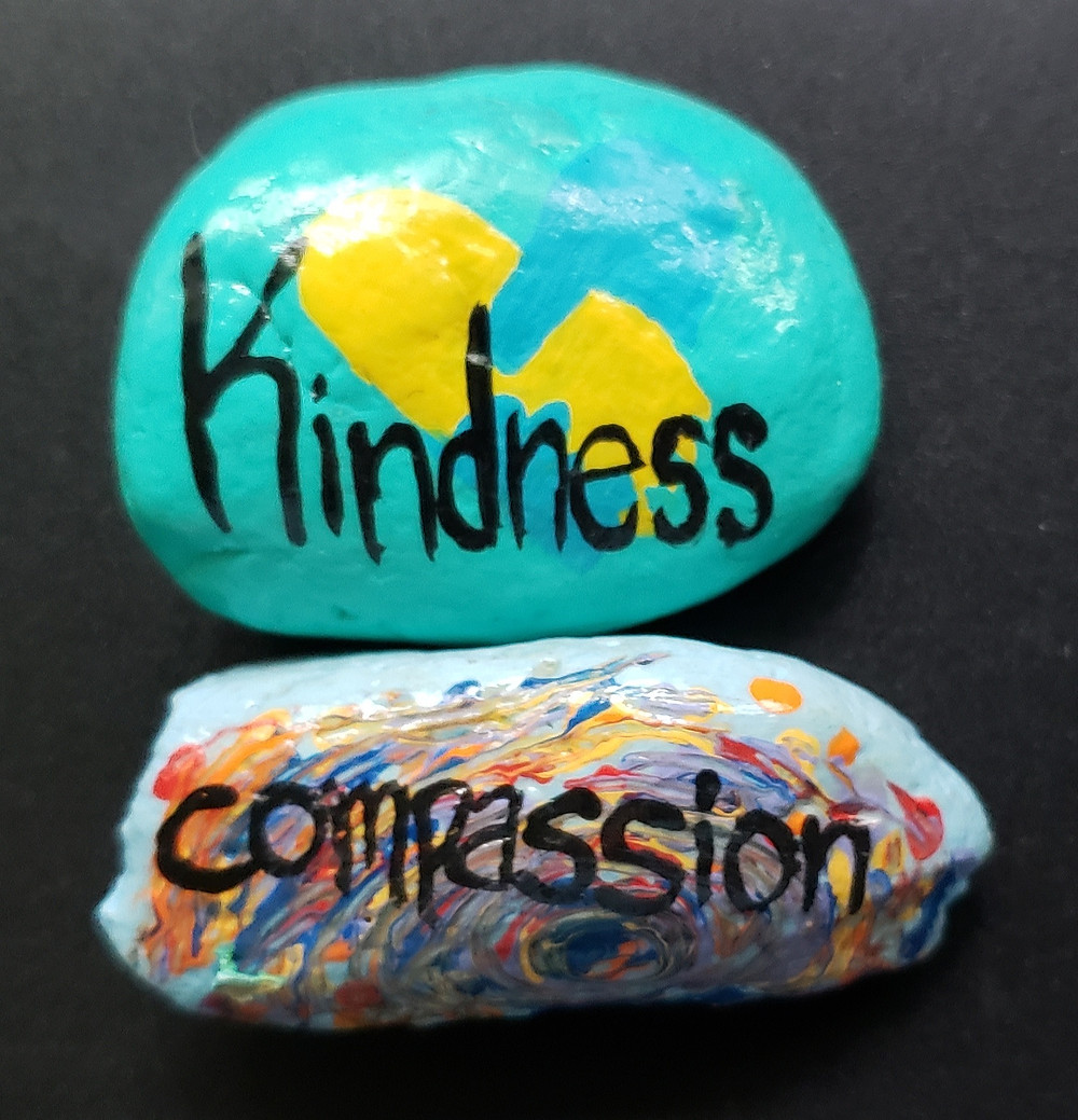 """A black background with two painted rocks. The one on top is painted bright teal-blue and has a yellow and darker blue silhouette of two hands holding with """"Kindness"""" in black paint on top. The second rock, below the first, is a light blue with a rainbow of other colors and the word """"compassion"""" in black paint on top."""
