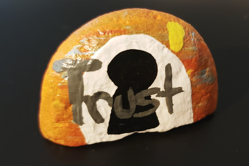 """A black background with a painted rock. The rock has an orange background with white and black creating the image of a keyhole. The word """"trust"""" is on top in gray paint."""