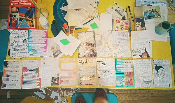 """This is an overhead shot of my incredibly messy desk, halfway through the production phase of the first issue of """"Atrocities Against Indigenous Canadians for Dummies."""" There are papers and zine pages everywhere as well as my coffee cup, my moccasins in the whot. My table is a yellow, 1950's table and my chairs are chrome with blue vinyl"""