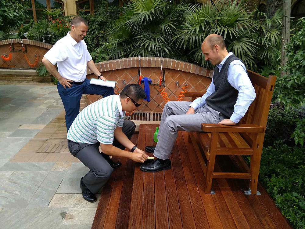 Patrick Quernemoen tests out the new Shoeshine service.  Jimmy Han shoes how it's done while Stan