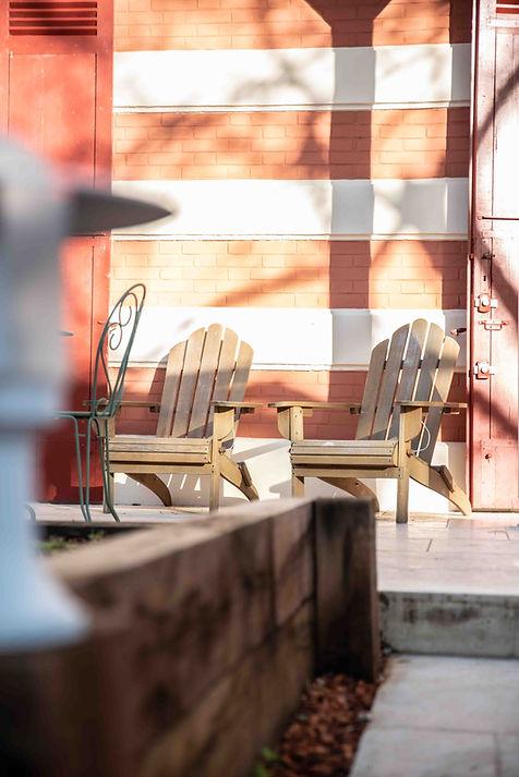 détails du mobilier de jardin avec ses fauteuils de bois Adirondack et ses chaises Fermob