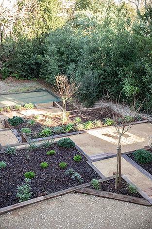 le jardin en terrasses et ses bastaings de bois du jardin côté bassin