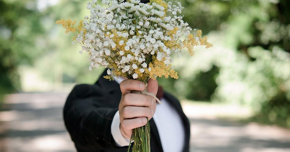 hombre_aguantando_un _ramo_de_flores_frente_a_su_cara