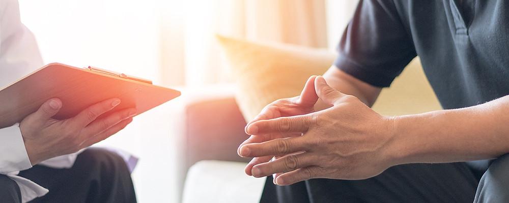 hombre sentado en el mueble durante una sesión de terapia con su psicólogo