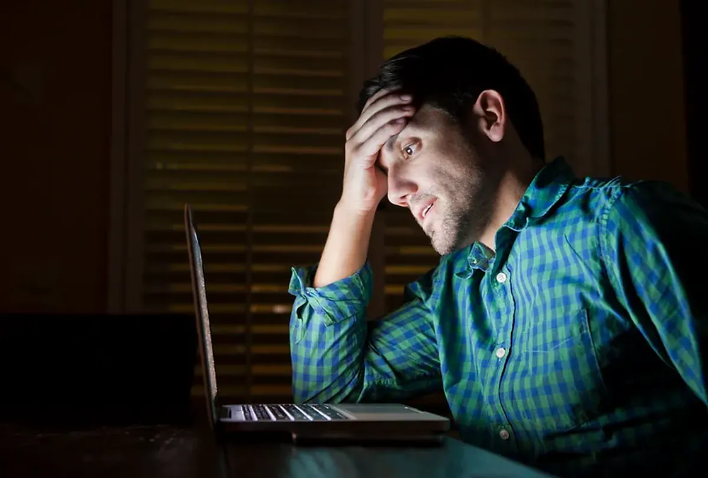 hombre_estresado_frente_a_computadora_de_noche