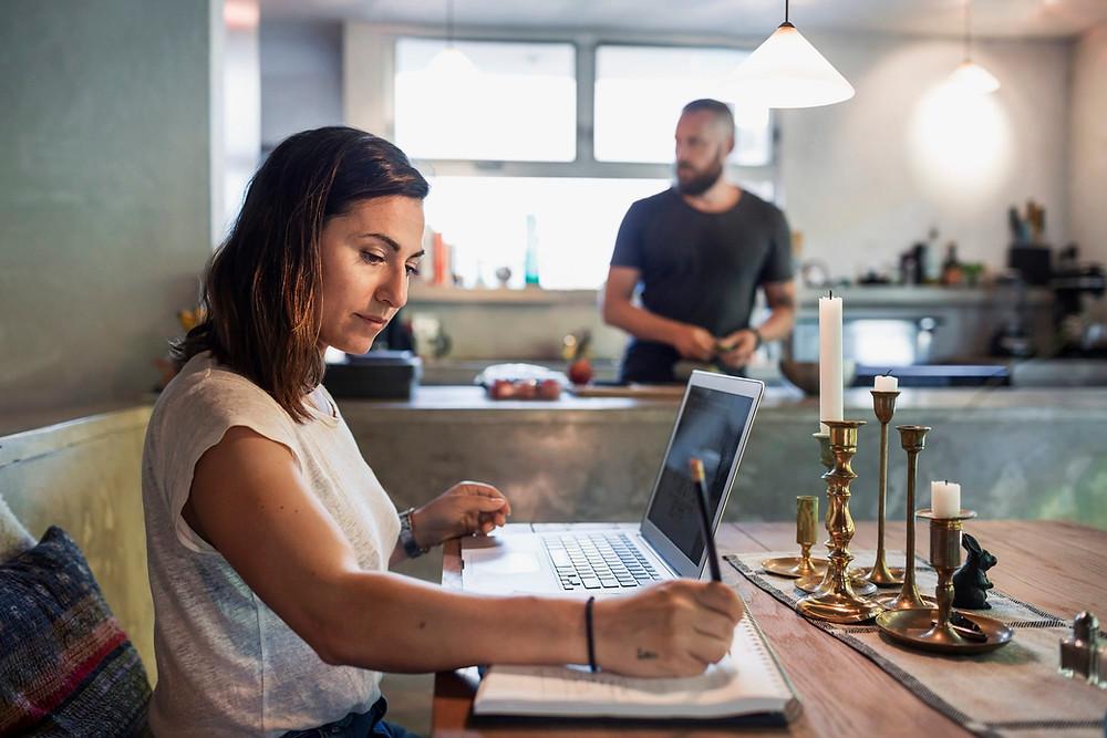 Mujer trabajando remoto en su hogar con la computadora de frente