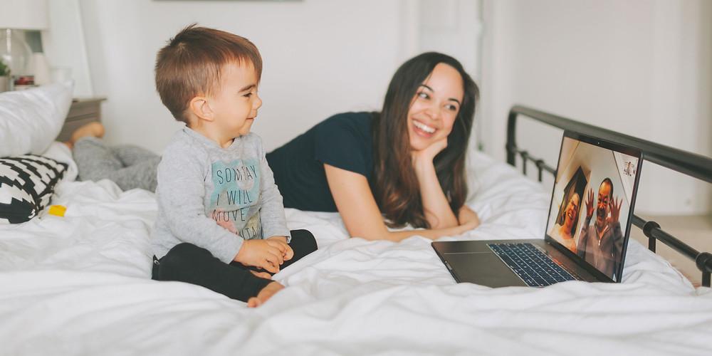 Mujer acostada en la cama con su hijo realizando una videoconferencia en tiempos de pandemia utilizando su computadora