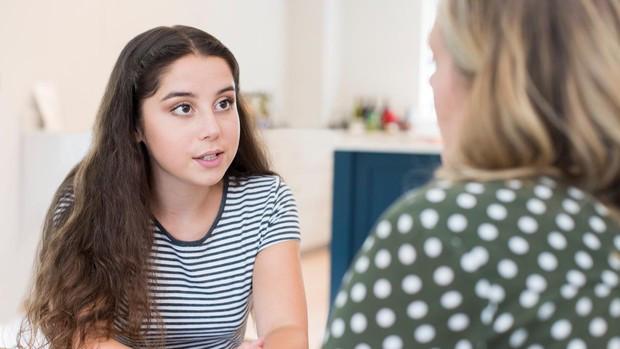 Jóven sentada hablando con su madre