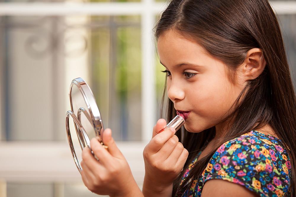 niña_con_espejo_pintandose_los_labios