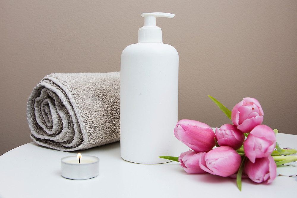 Home Spa Items - Towel, Lit Candle, Flowers, Lotion Bottle