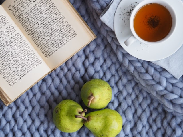 A book, green pears and a cup of tea on a blue mat
