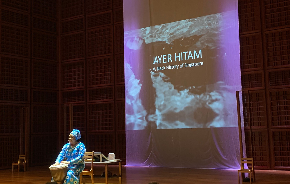 Woman drumming with banner behind reads: Ayer Hitam - A Black History of Singapore