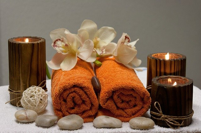 Spa Setting: Rolled Towels, Lit Candles, Stones, Orchids
