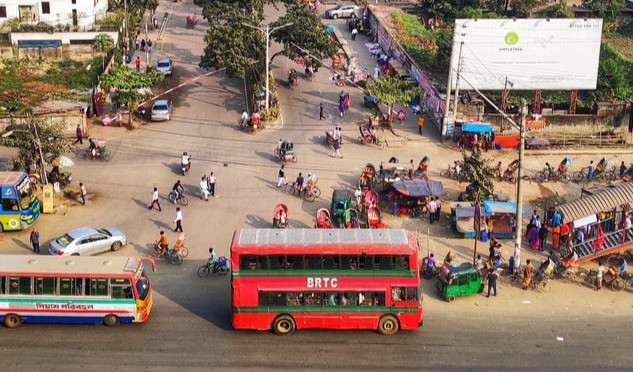 Intersection in Dhaka with bus, and other vehicles