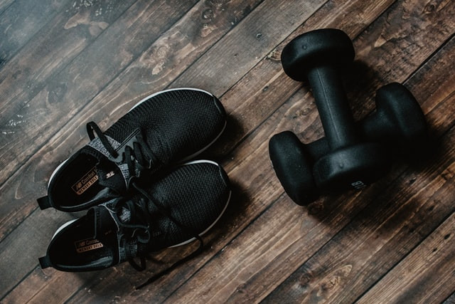 Black sneakers and dumbells on a wooden floor