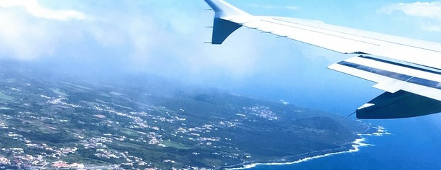 Airplane wing overlooking a coastal shore